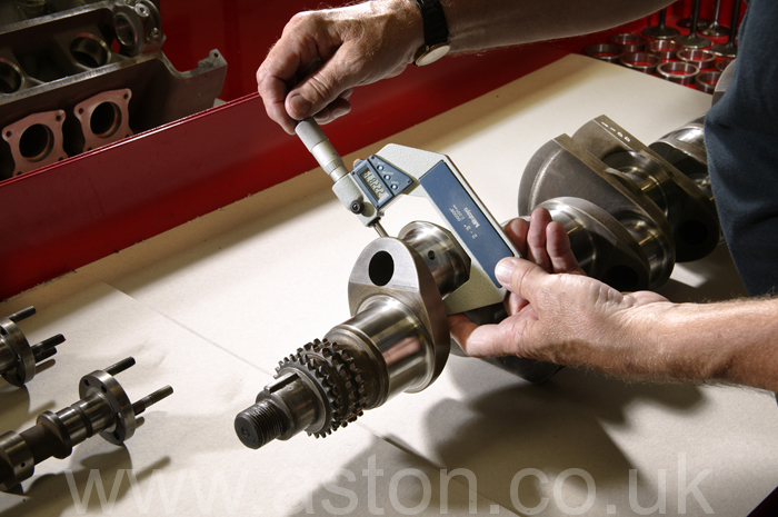 Using a micrometer to measure main bearing wear and surface finish. Main bearing wear is the usual cause of low oil pressure